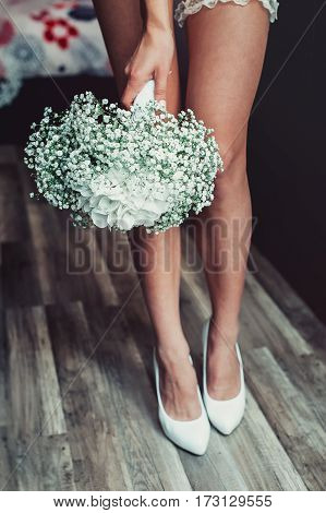 wedding bouquet of white gypsophila and hydrangea in a hand of naked bride