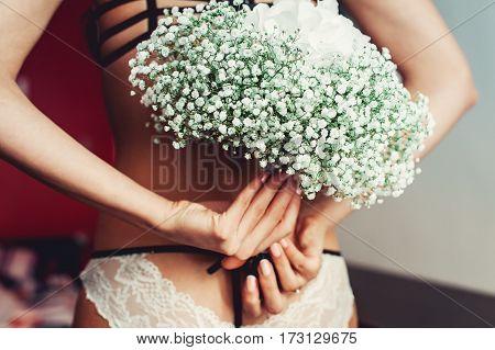 wedding bouquet of white gypsophila and hydrangea on the naked bride back