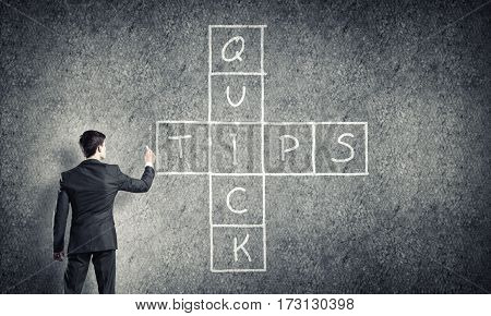 Businessman standing with back and drawing crossword on blackboard