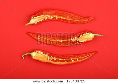 Three Cut Hot Chili Peppers On Red Background