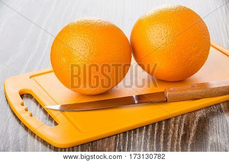 Two Ripe Oranges And Kitchen Knife On Plastic Cutting Board