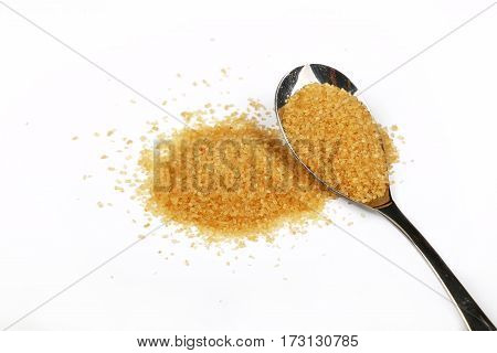 Full Spoon And Pinch Of Brown Cane Sugar On White