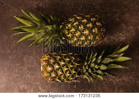 Two ripe pineapple lying on a dark marble table. Delicious fruit. Healthy eating. Pineapple on table