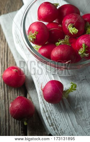 Red radish in a glass bowl on a wooden stand vertical