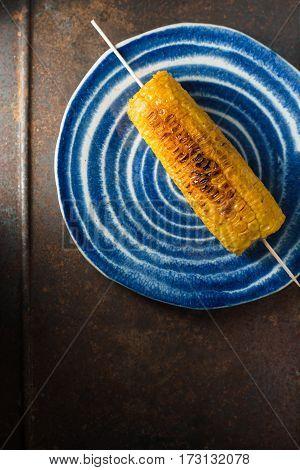 Roasted corn on blue ceramic plate vertical