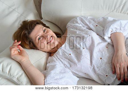An adult woman lying on the sofa