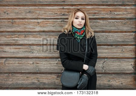Stylish Beautiful Young Woman In A Black Coat Standing Near The Vintage Wooden Wall
