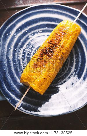 Roasted corn with salt on blue plate closeup vertical