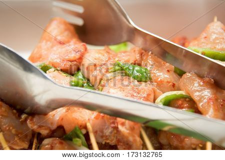 Raw marineted chicken on skewers for kebabs .