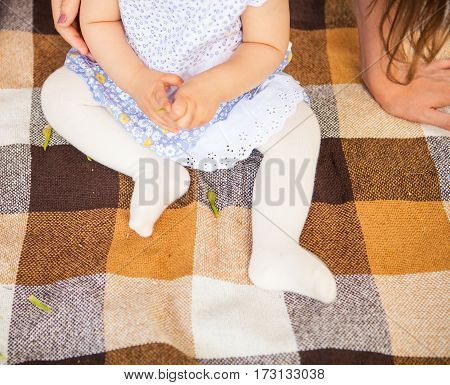 Outdoor portrait of a baby on all fours. crawling on knees child on the grass in a summer park set