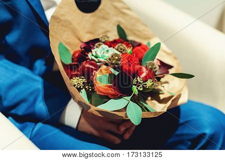 fiance holding a wedding bouquet made of red and biege peony wrapped in paper