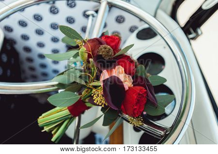 wedding bouquet of red and biege peony on a chrome wheel of retro car