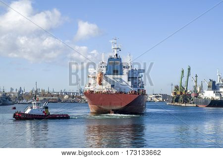 Tug boat towing container ship in harbor in sunny day