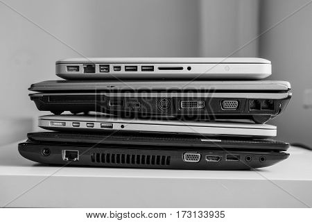 The different laptops placed on a table on a roll. Horizontal indoors shot.