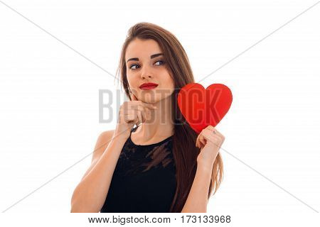 young charming brunette woman in stylish black dress with red heart in her hands looking away isolated on white