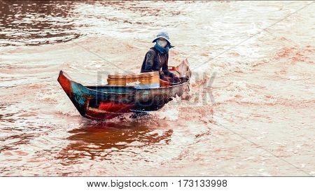 Tonle Sap Lake Siem Reap Cambodia - July 13 2013: Cambodian people live on Tonle Sap Lake in Siem Reap Cambodia. Woman riding on a motorboat