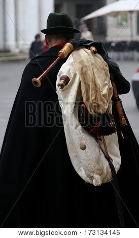 Bagpiper With A Black Cape And The Bagpipes On The Shoulders