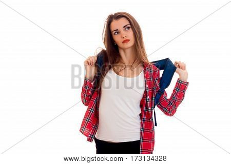 stylish tired brunette student girl with blue backpack looking away and posing on camera isolated on white