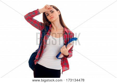 stylish tired brunette student girl with blue backpack and folder for notebooks in her hands looking at the camera isolated on white