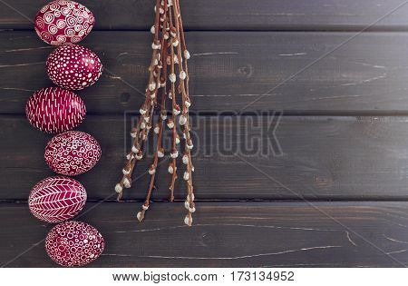 Still life with Pysanka decorated Easter eggs dry willow branches on black wooden background top view copy space