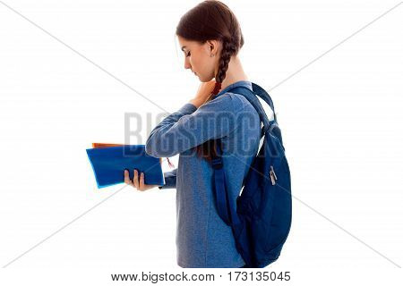 profile of stylish happy brunette student girl with blue backpack and folder for notebooks in her hands posing isolated on white