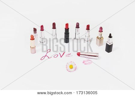 Lipstick lie on white background. Female lip pencil. Kiss of lips on paper. The word love written in lipstick. Reflection of lipstick in the mirror. View from above. Concept. Decorative cosmetics