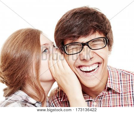 Pretty girl whispering secret in ear of her laughing friend isolated on white background - friendship concept