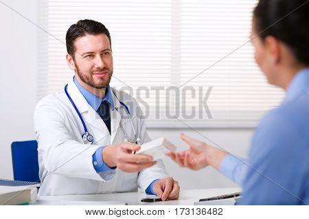 Doctor Passing Medicine To Patient