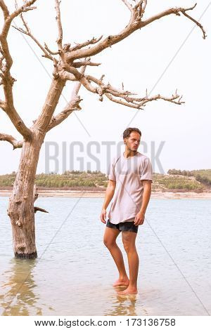 handsome young taned male model stood under a dying tree in a flooded lakeconcept of climate change. filter added blank sky in background for copy space