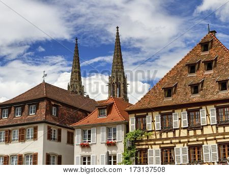 Saints-Pierre-et-Paul church towers and half-timberedr houses by day, Obernai, France