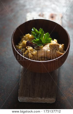 Pilaf with rice, chicken and raisins in a wooden bowl vertical
