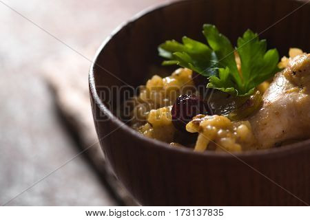 Pilaf with rice, chicken and raisins in a wooden bowl closeup horizontal