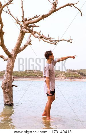 young man pointing mimicking the dying tree in a flooded lakefilter added blank sky in background for copy space