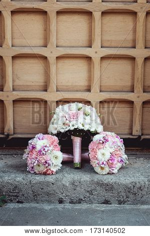 three wedding bouquets of white and biege roses on the floor. brides and bridesmaids.