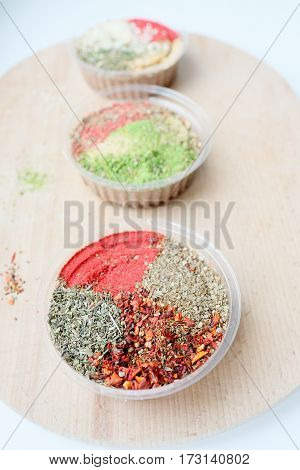 Three jars with a mix of oriental spices on a light background. The focus of one jar the rest are blurred. Is suitable for the cooking and articles of oriental spices.