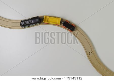 Toy train and wooden rails on white background. Top view.