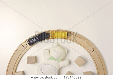 Toys frame with teddy bear, wooden cubes and toy train on the white background. Top view