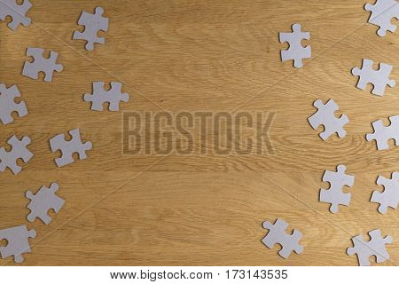 Puzzle game paper pieces pattern frame on wooden background. Top view. Copy space for text. Toned picture