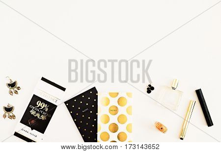Beauty products accessories polka dot notepads dark chocolate top view. Still life. Gold black and white glamour style