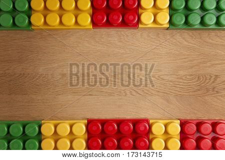 Colorful bright plastic construction blocks on wooden background as frame. Top view. Copy space for text