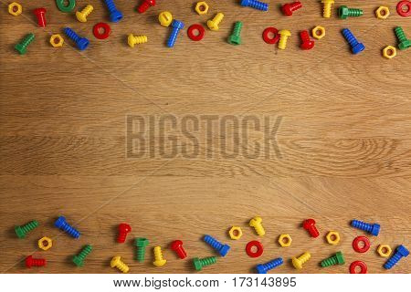 Kids toys tools: colorful screws and nuts on wooden background. Top view. Flat lay.