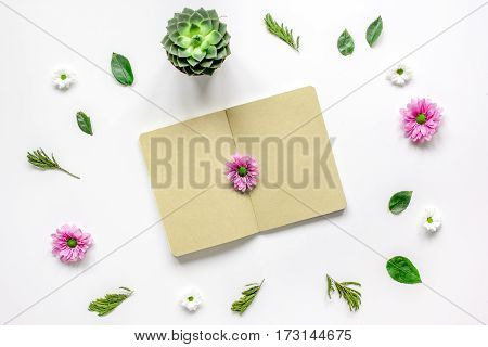 Craft paper notebook with flower petals on white table background top view mock-up
