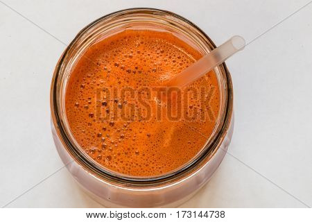 Fresh carrot juice in bottles on a white wooden table.