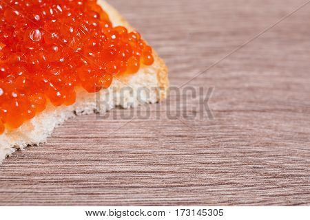Red caviar on a sandwich on the table. Healthy food. Fish appetizer. Russian kitchen. Space for the design for the text.