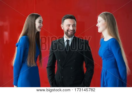Business team at presentation. a man and two women on a red background.