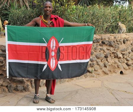 AMBOSELI, KENYA - OCT 13: Unidentified African man from Masai tribe waving a Kenyan flag on Oct 13, 2011 in Masai Mara, Kenya. They are nomadic and live in small villages.