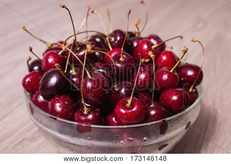 Summer berries. Ripe juicy red cherry with drops of water in a transparent plate on a wooden background. Berries in a bowl. Berries on wooden background