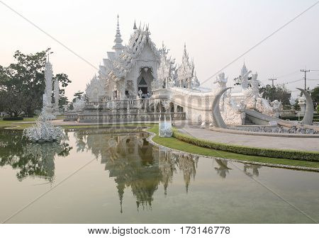 CHIANG RAI, THAILAND -  February 27, 2010: beautiful and amazing Wat Rongkhun (White temple) is reflected in the lake. White temple, Chiang Rai, Thailand.