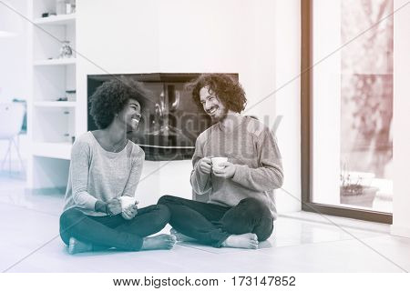 Young romantic multiethnic couple sitting on the floor in front of fireplace at home, looking at each other, talking and drinking coffee autumn day