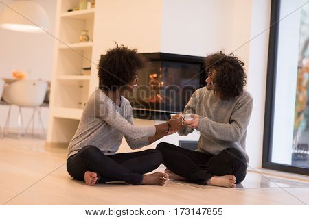 Young romantic multiethnic couple sitting on the floor in front of fireplace at home, looking at each other, talking and drinking coffee at autumn day